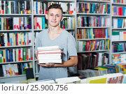 Купить «Portrait of glad teenager boy with book pile», фото № 25900756, снято 16 сентября 2016 г. (c) Яков Филимонов / Фотобанк Лори