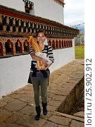 Fruchtbarkeitsritual und Phallus-Kult, junge japanische Frau umrundet den Tempel mit einem Phallus im Arm, Kloster Chime Lhakhang bei Lobesa, Bhutan /... Стоковое фото, фотограф Zoonar/GFC Collectio / age Fotostock / Фотобанк Лори
