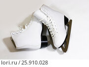 Купить «Pair of women's white figure ice skates on white background», фото № 25910028, снято 22 января 2017 г. (c) Виктория Кузьменкова / Фотобанк Лори