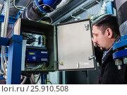 Специалист осматривает прибор учёта тепла на теплорегулирующей подстанции, фото № 25910508, снято 31 марта 2017 г. (c) Вадим Орлов / Фотобанк Лори