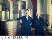 Купить «Two happy men in uniforms standing in winery fermentation compartment», фото № 25913440, снято 15 сентября 2019 г. (c) Яков Филимонов / Фотобанк Лори