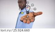 Digital composite of businessman holding various icons connected to light bulb. Стоковое фото, агентство Wavebreak Media / Фотобанк Лори