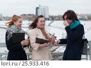 Купить «Три веселые девушки с блокнотами смеются на набережной в Тюмени зимой», эксклюзивное фото № 25933416, снято 6 апреля 2017 г. (c) Землянникова Вероника / Фотобанк Лори