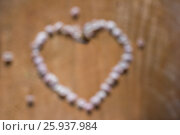 Unfocused heart made of gentle pink petals on cracked brown wooden background. Стоковое фото, фотограф Жданова Дарья Юрьевна / Фотобанк Лори