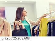 Купить «happy young woman choosing clothes in mall», фото № 25938608, снято 19 февраля 2016 г. (c) Syda Productions / Фотобанк Лори