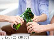 Купить «close up of friends clinking beer bottles at home», фото № 25938708, снято 22 марта 2014 г. (c) Syda Productions / Фотобанк Лори