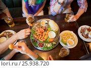 Купить «friends eating and drinking at bar or pub», фото № 25938720, снято 14 июля 2016 г. (c) Syda Productions / Фотобанк Лори
