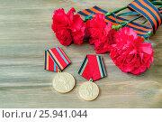 Купить «9 мая. Юбилейные медали в честь Победы в Великой Отечественной войне, красные гвоздики и георгиевская лента на деревянном столе», фото № 25941044, снято 2 апреля 2017 г. (c) Зезелина Марина / Фотобанк Лори