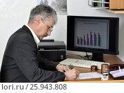 Купить «Инженер-архитектор у компьютера, за рабочим столом ставит подпись под документом», фото № 25943808, снято 2 апреля 2017 г. (c) Сергей Галинский / Фотобанк Лори