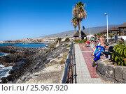 Купить «Пешеходная дорожка со скамейками вдоль вулканического побережья Атлантического океана. Город Costa Adeje, Тенерифе, Канарские острова, Испания», фото № 25967920, снято 31 декабря 2015 г. (c) Кекяляйнен Андрей / Фотобанк Лори
