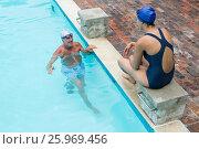 Купить «Senior man interacting with woman at poolside», фото № 25969456, снято 12 декабря 2016 г. (c) Wavebreak Media / Фотобанк Лори