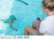 Купить «Female trainer monitoring time of boy swimming in pool», фото № 25969468, снято 12 декабря 2016 г. (c) Wavebreak Media / Фотобанк Лори