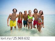 Купить «Cheerful couples in beachwear standing in sea», фото № 25969632, снято 17 января 2017 г. (c) Wavebreak Media / Фотобанк Лори