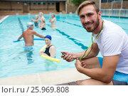 Купить «Smiling swim coach holding stopwatch near poolside», фото № 25969808, снято 12 декабря 2016 г. (c) Wavebreak Media / Фотобанк Лори