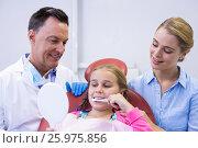 Купить «Dentist assisting young patient while brushing teeth», фото № 25975856, снято 11 декабря 2016 г. (c) Wavebreak Media / Фотобанк Лори