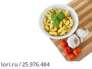Купить «High angle view of pasta served in bowl on cutting board», фото № 25976484, снято 21 октября 2016 г. (c) Wavebreak Media / Фотобанк Лори