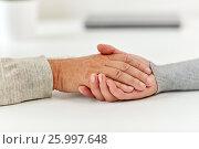 Купить «close up of old man and young woman holding hands», фото № 25997648, снято 7 июля 2016 г. (c) Syda Productions / Фотобанк Лори