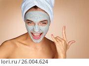 Купить «Funny woman wearing a facial mask and making rock hand gesture. Portrait of young woman on on beige background. Skin care concept», фото № 26004624, снято 13 мая 2016 г. (c) Роман Егошин / Фотобанк Лори
