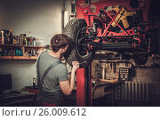 Купить «Mechanic working on classic car wheels and suspension in restoration workshop», фото № 26009612, снято 6 апреля 2017 г. (c) Andrejs Pidjass / Фотобанк Лори