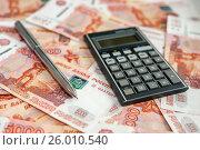 Купить «Шариковая ручка и карманный калькулятор на фоне российских денег», эксклюзивное фото № 26010540, снято 16 апреля 2017 г. (c) Игорь Низов / Фотобанк Лори