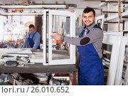 Купить «Young guy worker is demonstrating the window frame», фото № 26010652, снято 30 марта 2017 г. (c) Яков Филимонов / Фотобанк Лори