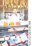 Купить «Seller offering displayed sorts of meat», фото № 26018744, снято 2 января 2017 г. (c) Яков Филимонов / Фотобанк Лори
