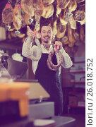 Купить «Smiling male seller showing sausages», фото № 26018752, снято 2 января 2017 г. (c) Яков Филимонов / Фотобанк Лори
