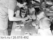 Купить «Воспитательница учит детей лепить виноград из пластилина. 1968 год.», эксклюзивное фото № 26019492, снято 19 апреля 2017 г. (c) Светлана Попова / Фотобанк Лори