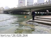 Китаец рыбак ловит рыбу сачком в реке Хайхе. Тяньцзинь. Китай (2017 год). Редакционное фото, фотограф Яна Королёва / Фотобанк Лори
