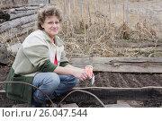 Купить «Женщина возле грядки собирается сеять морковь», фото № 26047544, снято 24 апреля 2013 г. (c) Светлана Попова / Фотобанк Лори