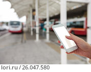Купить «Hand with mobile in the bus station», фото № 26047580, снято 14 октября 2019 г. (c) Wavebreak Media / Фотобанк Лори