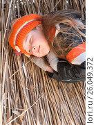Задумчивая девочка лежит на соломе. Стоковое фото, фотограф Юлия Мальцева / Фотобанк Лори