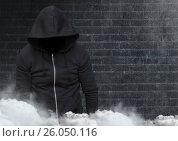 Купить «Anonymous criminal in hood in front of brick wall», фото № 26050116, снято 16 июля 2020 г. (c) Wavebreak Media / Фотобанк Лори