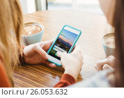 Купить «Young woman with phone in a cafeteria. Login screen», фото № 26053632, снято 19 августа 2018 г. (c) Wavebreak Media / Фотобанк Лори