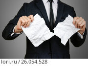 Купить «Businessman tearing hands crumpled sheet of A4 paper. Isolated on grey background», фото № 26054528, снято 18 апреля 2017 г. (c) Виктория Кузьменкова / Фотобанк Лори