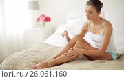 woman with feather touching bare legs on bed. Стоковое видео, видеограф Syda Productions / Фотобанк Лори