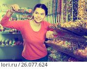 Купить «Girl studying assortment of marmalade and bonbons», фото № 26077624, снято 22 марта 2017 г. (c) Яков Филимонов / Фотобанк Лори