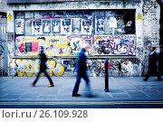 Tres personas irreconocibles andando por la acera de una calle y en la pared de fondo pintada con graffitis. Brick Ln, East End, London, UK, Europa. Стоковое фото, фотограф Lluís Real / age Fotostock / Фотобанк Лори