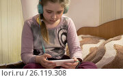 Купить «Girl with headphones listening to music from smartphone», видеоролик № 26119308, снято 24 апреля 2017 г. (c) Кузьмов Пётр / Фотобанк Лори