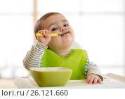 Купить «Happy baby boy spoon eats itself», фото № 26121660, снято 1 апреля 2017 г. (c) Оксана Кузьмина / Фотобанк Лори
