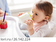 Купить «baby drinking from spout cup in highchair at home», фото № 26142224, снято 24 января 2017 г. (c) Syda Productions / Фотобанк Лори