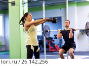 Купить «man and woman with weights exercising in gym», фото № 26142256, снято 19 февраля 2017 г. (c) Syda Productions / Фотобанк Лори