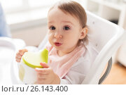 Купить «baby drinking from spout cup in highchair at home», фото № 26143400, снято 24 января 2017 г. (c) Syda Productions / Фотобанк Лори