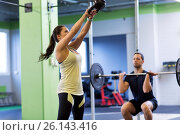 Купить «man and woman with weights exercising in gym», фото № 26143416, снято 19 февраля 2017 г. (c) Syda Productions / Фотобанк Лори