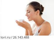 Купить «close up of happy woman holding and smelling cream», фото № 26143488, снято 9 апреля 2017 г. (c) Syda Productions / Фотобанк Лори