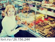 Купить «Woman selecting chocolates and confectionery», фото № 26156244, снято 31 марта 2020 г. (c) Яков Филимонов / Фотобанк Лори