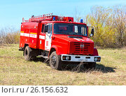 Купить «Red fire truck EMERCOM of Russia parked up on the spring field», фото № 26156632, снято 30 апреля 2017 г. (c) FotograFF / Фотобанк Лори