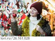 Купить «Positive young girl choosing Christmas decoration», фото № 26161028, снято 12 декабря 2016 г. (c) Яков Филимонов / Фотобанк Лори