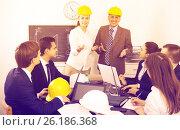 Купить «Successful professionals with laptops and helmets», фото № 26186368, снято 7 декабря 2019 г. (c) Яков Филимонов / Фотобанк Лори