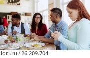 Купить «woman with smartphone and friends at restaurant», видеоролик № 26209704, снято 10 декабря 2018 г. (c) Syda Productions / Фотобанк Лори
